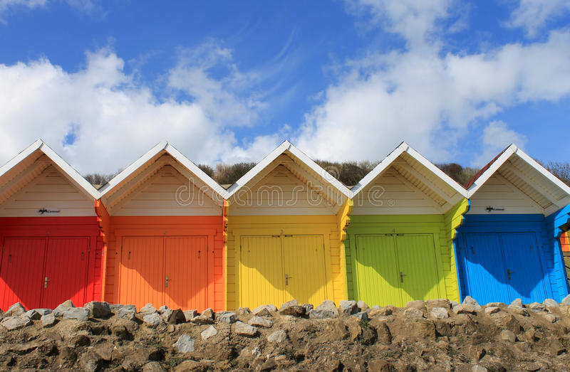 Colorful beach chalets. Row of colorful beach chalets with blue sky and cloudscape background, summer scene royalty free stock photos