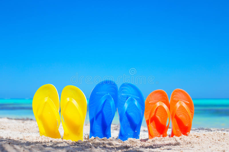 Colorful beach flip flops sandals on the beach royalty free stock photography