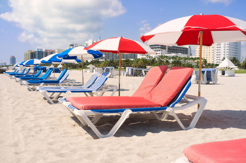 Colorful beach lounge chairs and umbrellas royalty free stock images
