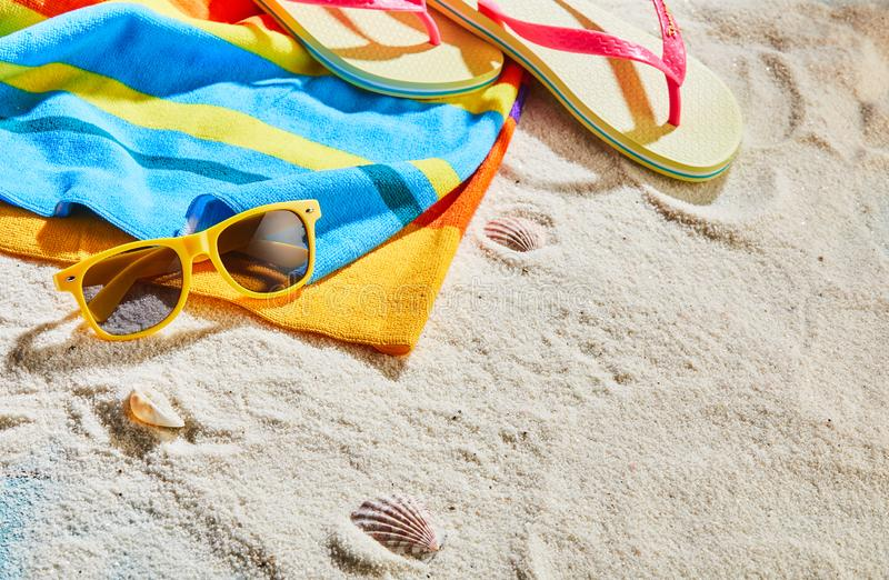Colorful beach towel, sunglasses and thongs. On white sand at the seaside in summer sunshine with copy space royalty free stock photos