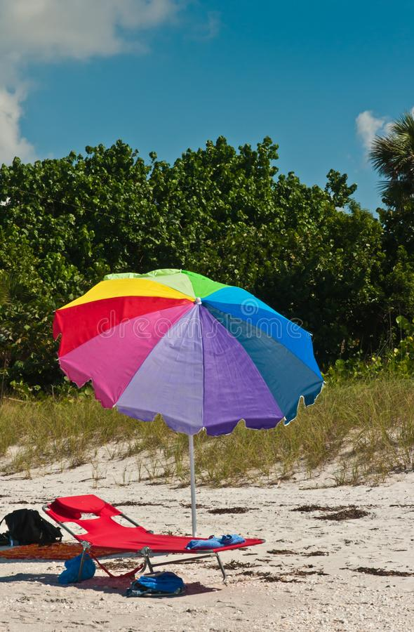 Colorful beach umbrella and beach lounge chairs royalty free stock images