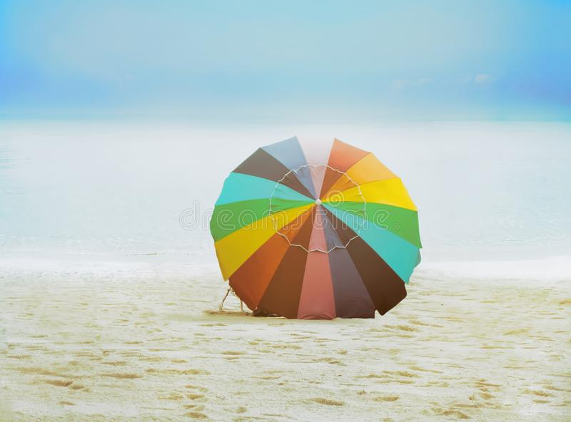 Colorful beach umbrella. Colorful beach umbrella on the sandy tropical beach royalty free stock photography