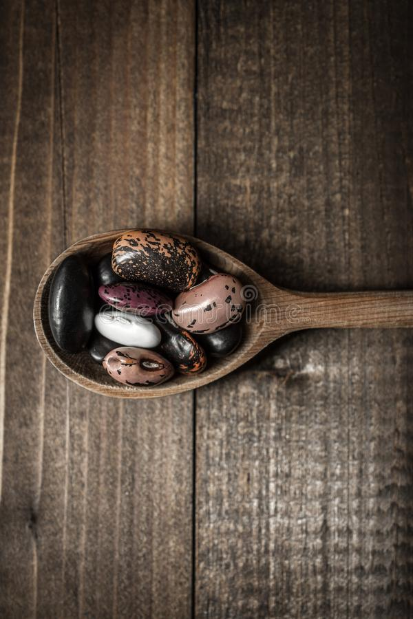 Colorful Spoons: Colorful Beans And Wooden Spoon On Dark Background Stock