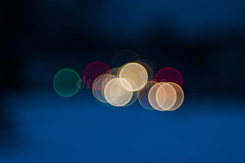 Colorful beautiful blurred bokeh background with copy space. Festive texture. Brilliant multicolored light spots on a dark blue stock photography