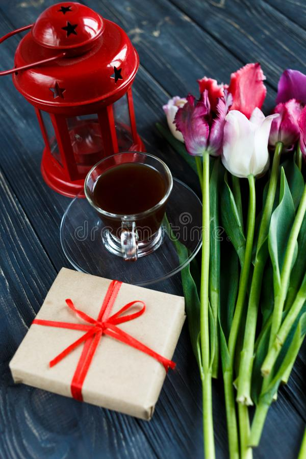 Colorful beautiful pink violet tulips and red lantern on gray wooden background. Valentines, spring background. floral mock up stock photo