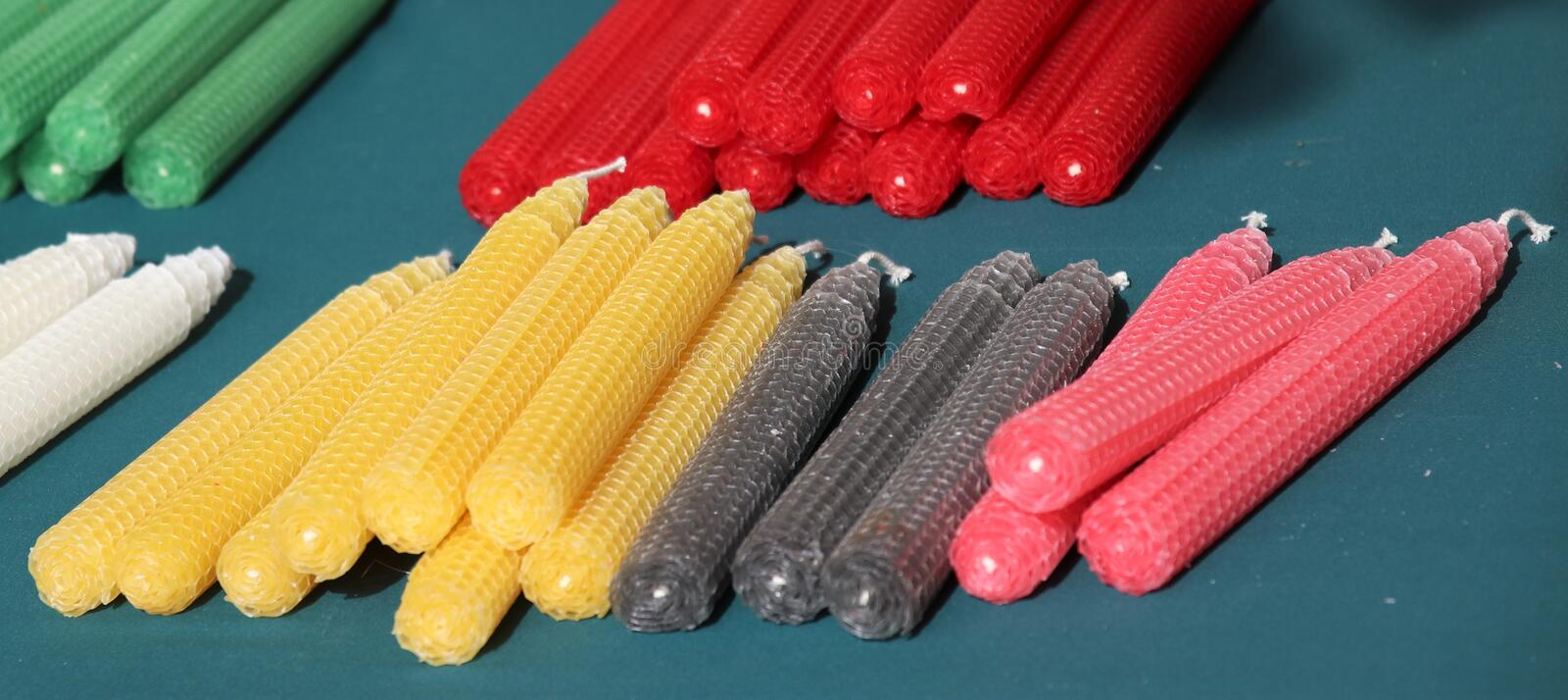 Colorful beeswax candles in a row. Colorful beeswax candles on a blue cloth. Candles are pink, gray, yellow, white and green. Selective focus royalty free stock photography