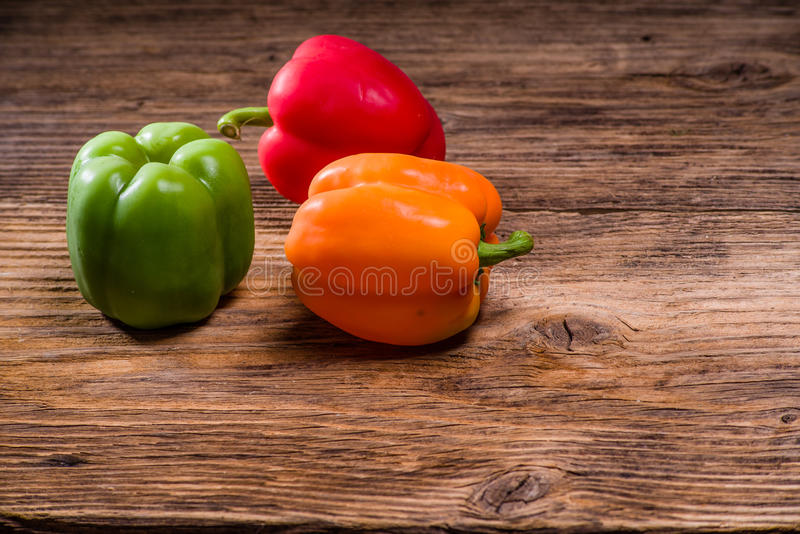 Colorful bell peppers on rustic table stock photos