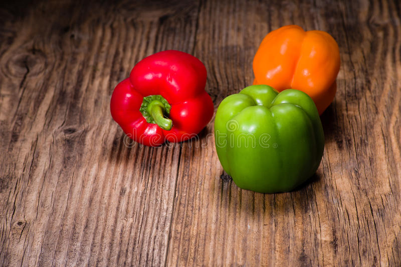 Colorful bell peppers on rustic table royalty free stock image