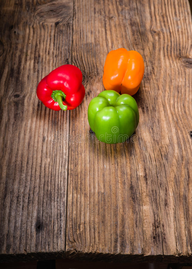 Colorful bell peppers on rustic table stock photo