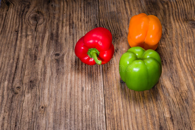 Colorful bell peppers on rustic table royalty free stock photography