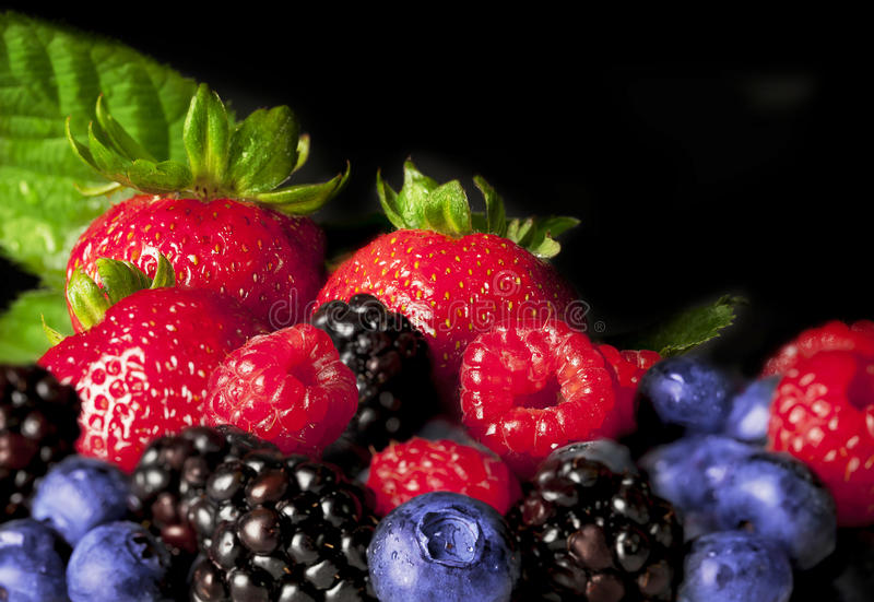 Colorful Berries. Including strawberries, blueberries, red raspberries and blackberries on black background