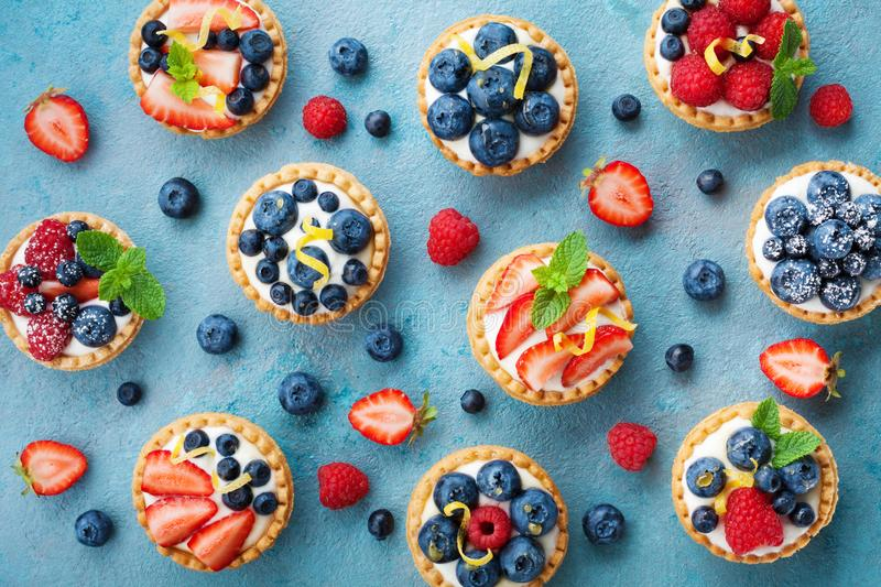 Colorful berry tartlets or cake for kitchen pattern. Pastry dessert from above. Colorful berry tartlets or cake for kitchen pattern. Pastry dessert top view royalty free stock photo