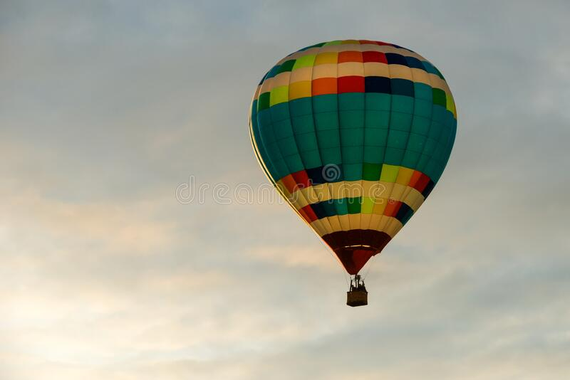Colorful big hot air balloon flying at sunset stock photography