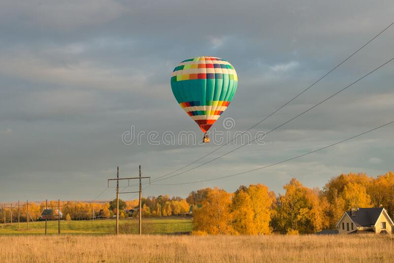 Autumn day, a big hot air  balloon  flies over the field royalty free stock photo
