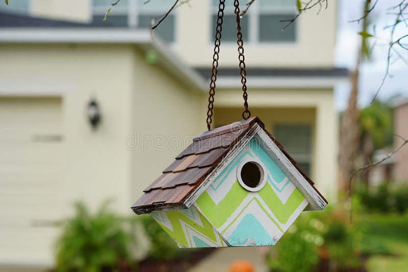 A colorful bird house with a new house in the background. A colored bird House, with a new house in the background, taken in florida, USA royalty free stock image