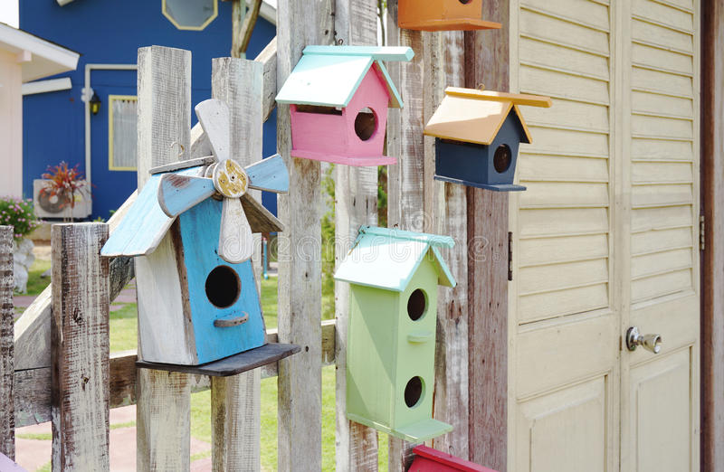 Colorful bird house on the timber fence. With louver door royalty free stock photography
