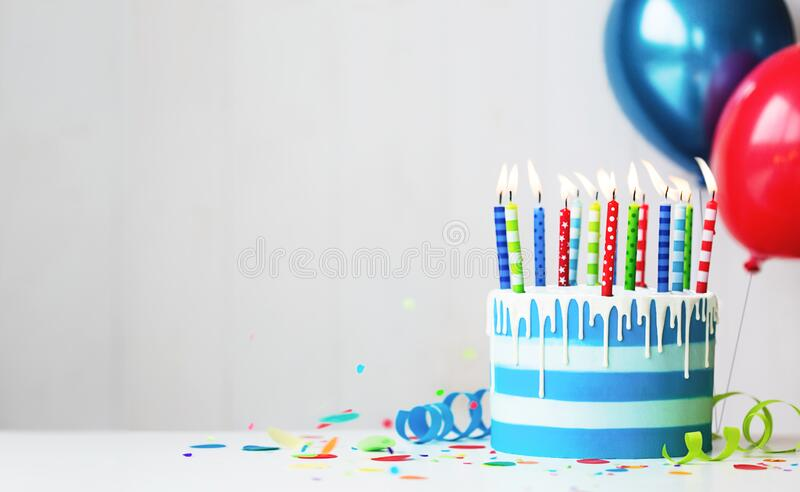 Colorful birthday cake with candles and balloons royalty free stock images