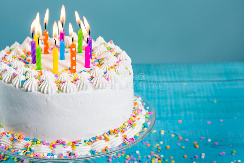 Colorful Birthday Cake with Candles. White Buttercream icing birthday cake with with colorful sprinkles and Candles over blue background royalty free stock photos