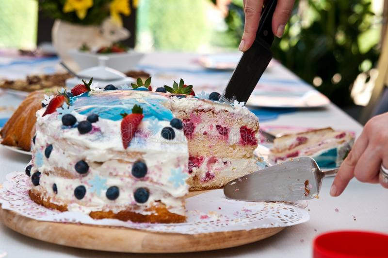 Colorful birthday cake. Cutting a colourful birthday cake royalty free stock photography