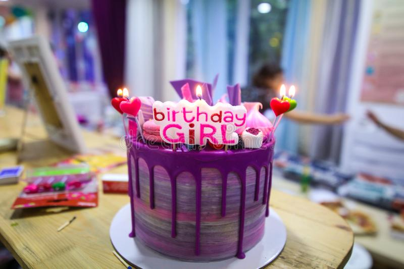 Colorful birthday cake with the message Birthday Girl and lit candles on it stock photos