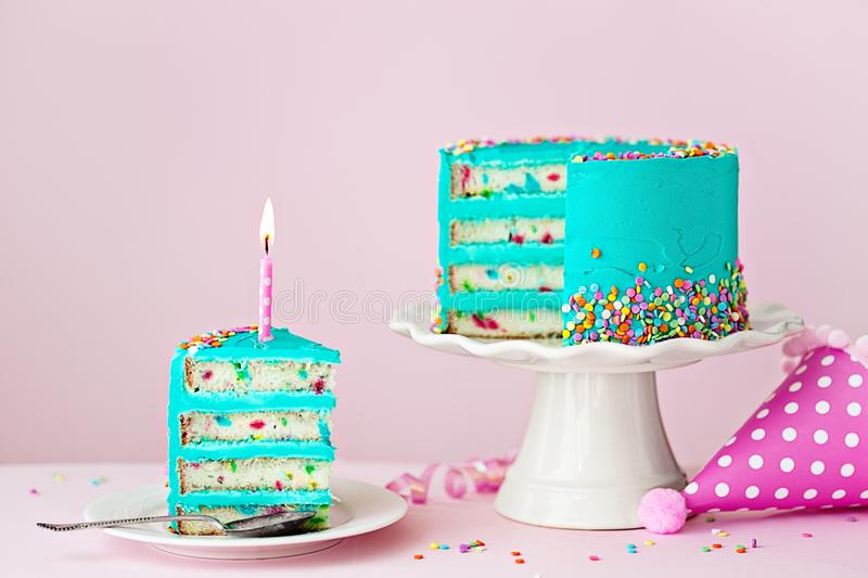 Colorful birthday cake with one candle. Colorful birthday cake with one slice and a candle stock photos