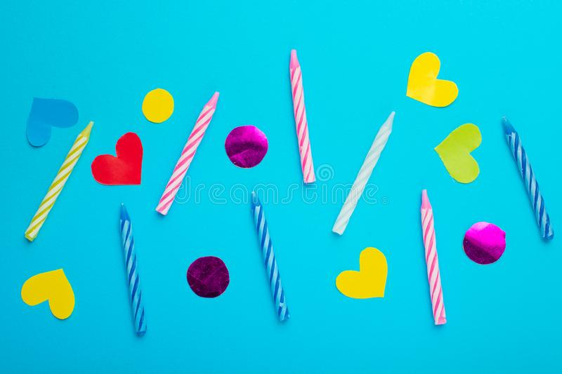 Colorful birthday candles on blue background, flat lay, top view.  stock photos