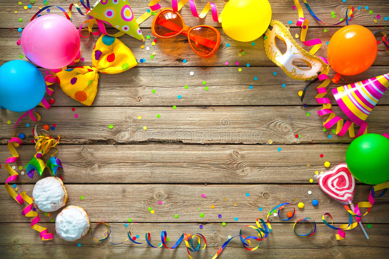 Colorful birthday or carnival background. Colorful birthday or carnival frame with party items on wooden background stock photo