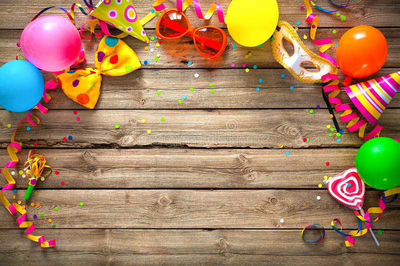 Colorful birthday or carnival background. Colorful birthday or carnival frame with party items on wooden background royalty free stock photos