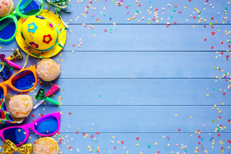 Colorful birthday or carnival border with party items on wooden background royalty free stock photography