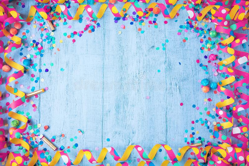 Colorful birthday or carnival frame with party items on wooden background. royalty free stock image