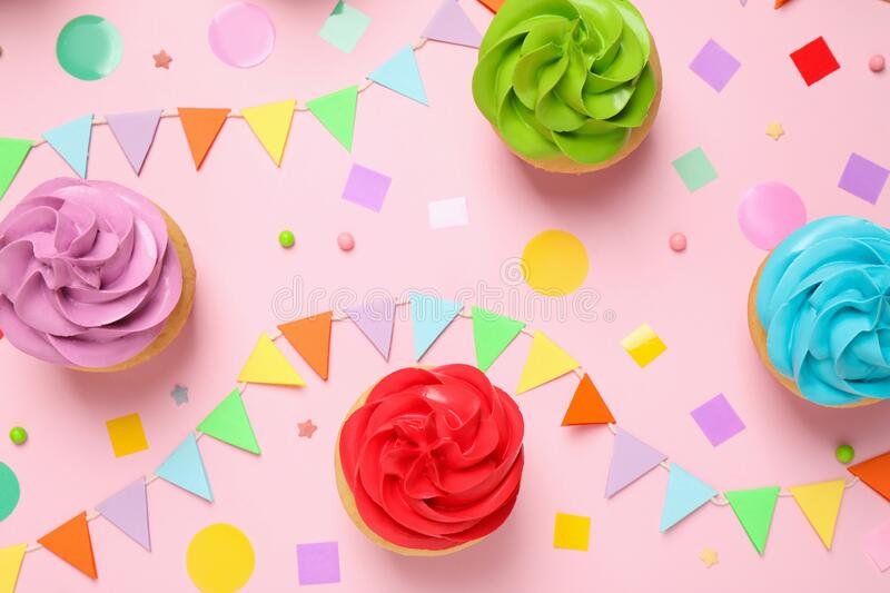 Colorful birthday cupcakes on light pink, flat lay royalty free stock image