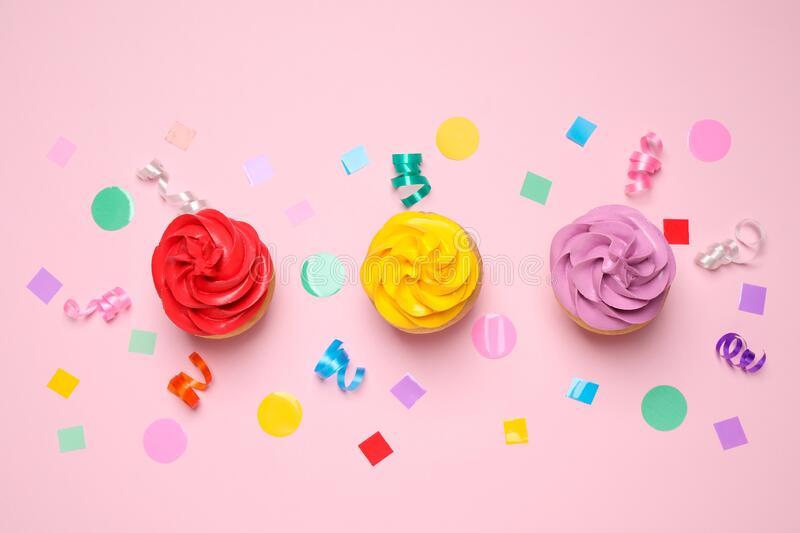 Colorful birthday cupcakes on light pink, flat lay royalty free stock images