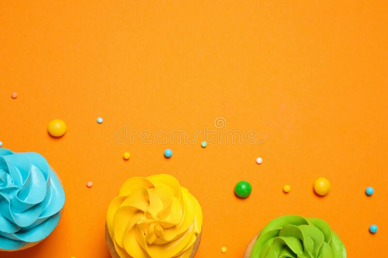 Colorful birthday cupcakes on background, flat lay. Space for text stock photos
