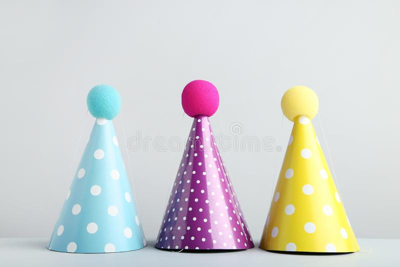 Birthday paper caps. Colorful birthday paper caps on grey background stock photos