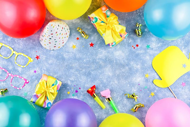 Colorful birthday party accessories on blue. Wrapped gifts, confetti, balloons, party hats, decorations, copy space. Birthday party accessories and event stock photos