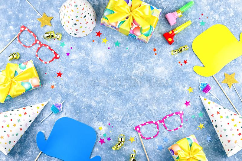 Colorful birthday party accessories on blue. Wrapped gifts, confetti, balloons, party hats, decorations, copy space. Birthday party accessories and event royalty free stock photo