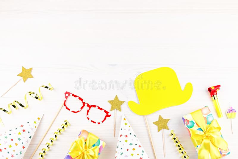 Colorful birthday party accessories on white. Wrapped gifts, confetti, balloons, party hats, decorations, copy space. Birthday party accessories and event royalty free stock photo