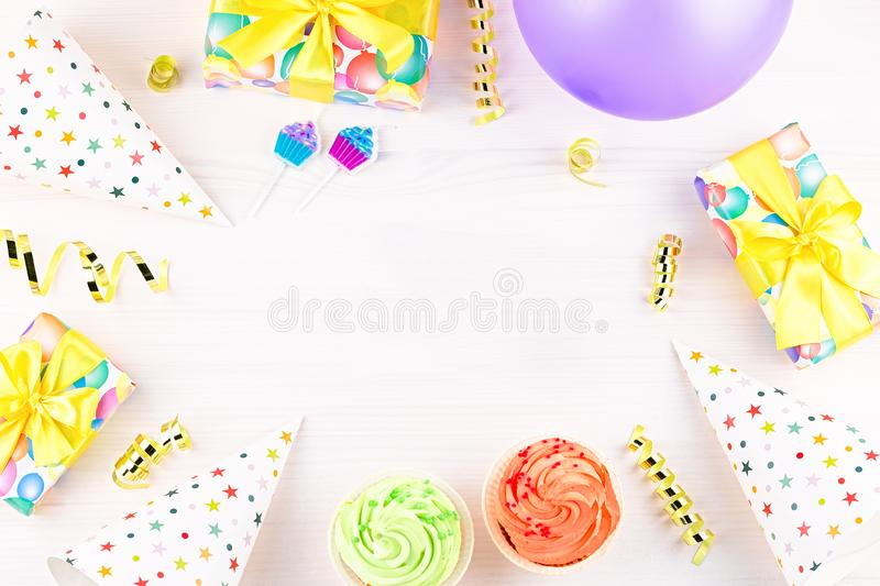 Colorful birthday party accessories on white. Wrapped gifts, confetti, balloons, party hats, decorations, copy space. Birthday party accessories and event stock photos