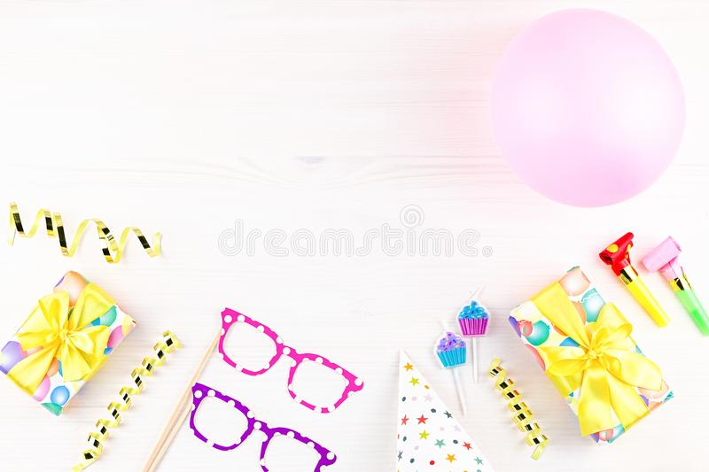 Colorful birthday party accessories on white. Wrapped gifts, confetti, balloons, party hats, decorations, copy space. Birthday party accessories and event stock photo