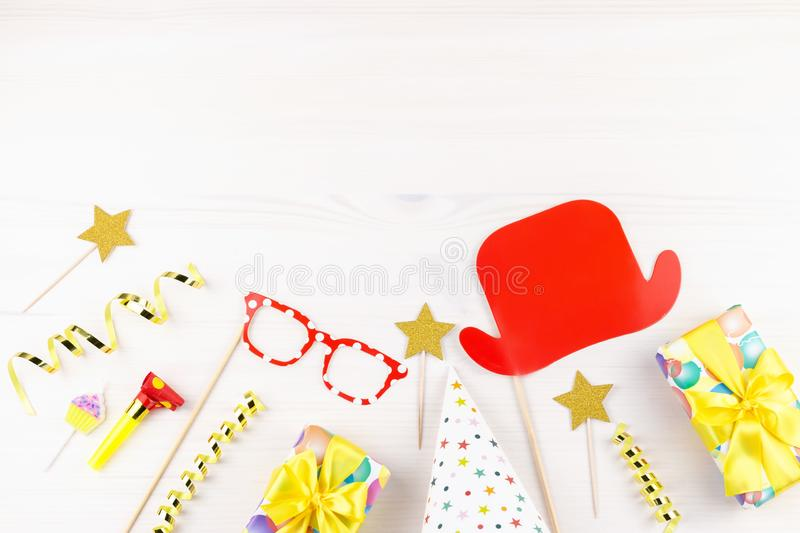 Colorful birthday party accessories on white. Wrapped gifts, confetti, balloons, party hats, decorations, copy space. Birthday party accessories and event stock images