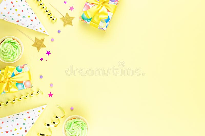 Colorful birthday party accessories on yellow. Wrapped gifts, confetti, balloons, party hats, decorations, copy space. Birthday party accessories and event royalty free stock photos