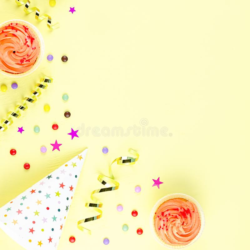 Colorful birthday party accessories on yellow. Wrapped gifts, confetti, balloons, party hats, decorations, copy space. Birthday party accessories and event royalty free stock image