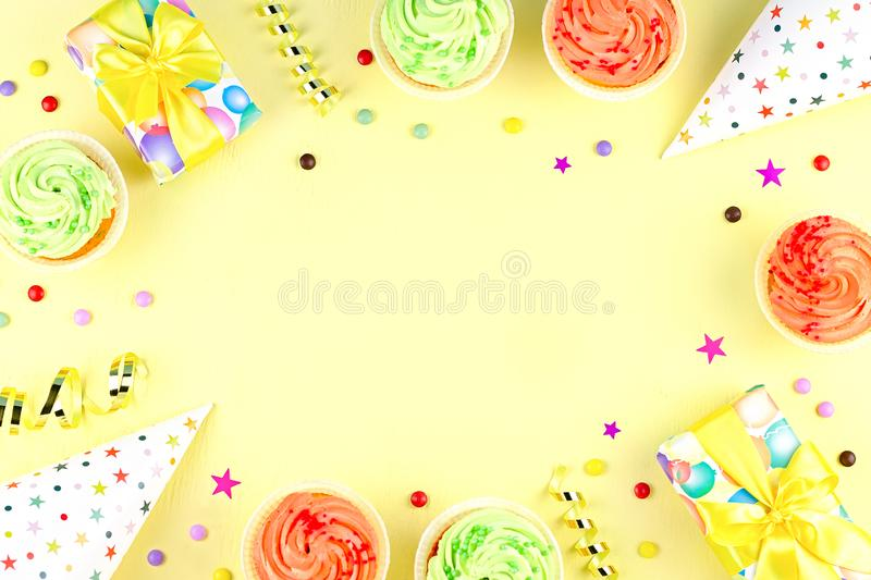 Colorful birthday party accessories on yellow. Wrapped gifts, confetti, balloons, party hats, decorations, copy space. Birthday party accessories and event stock photography