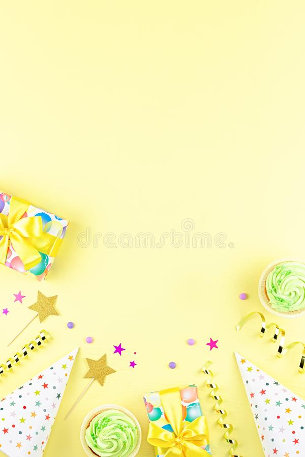 Colorful birthday party accessories on yellow. Wrapped gifts, confetti, balloons, party hats, decorations, copy space. Birthday party accessories and event stock image