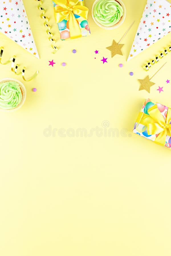 Colorful birthday party accessories on yellow. Wrapped gifts, confetti, balloons, party hats, decorations, copy space. Birthday party accessories and event stock photo