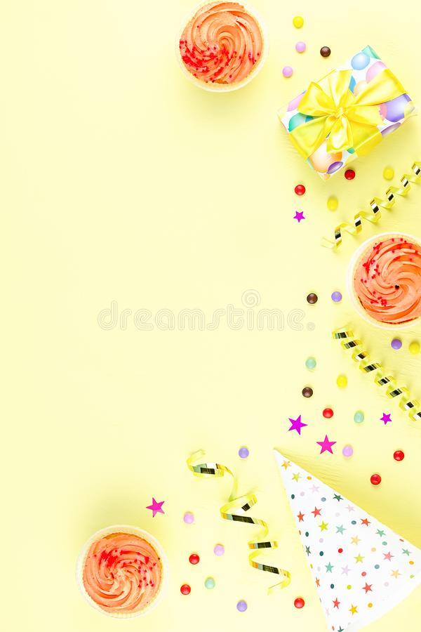 Colorful birthday party accessories on yellow. Wrapped gifts, confetti, balloons, party hats, decorations, copy space. Birthday party accessories and event royalty free stock images