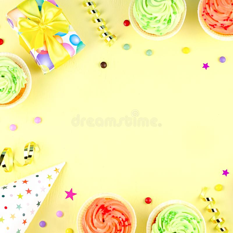 Colorful birthday party accessories on yellow. Wrapped gifts, confetti, balloons, party hats, decorations, copy space. Birthday party accessories and event stock images