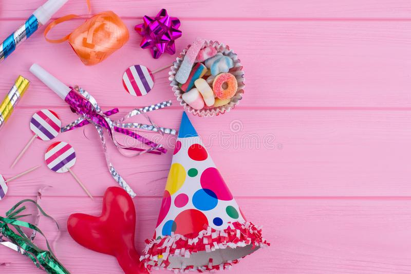 Colorful Birthday party supplies on pink wood. stock photography