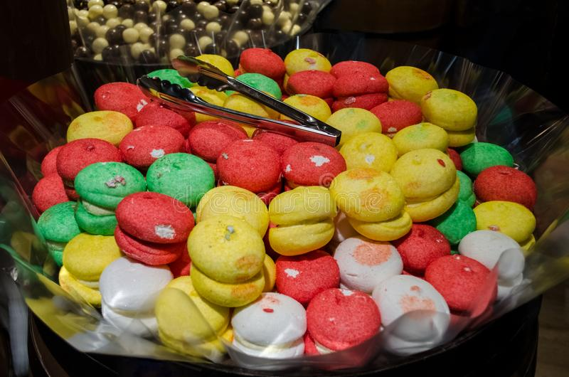 Colorful bizet sweets, round sugar candies. With tongs for sweets in big cask royalty free stock images