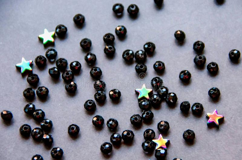 Colorful, black beads and stones isolated on grey background stock image